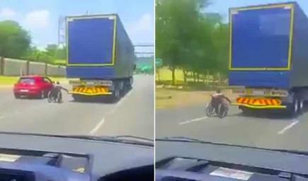 رجل مقعد يتنقل على مقعده المتحرك عبر امساكه بمؤخرة شاحنة مجازفا بحياته