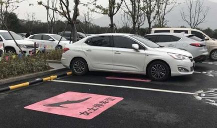 مواقف سيارات تم تمييزها برسم حذاء نسائي داخل مربع وردي اللون على الأرض