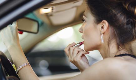 النساء تطبقن الماكياج وراء عجلة القيادة