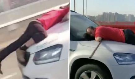 رجل غاضب يتعلق بغطاء سيارة لمسافة 13 كيلومتراً في الصين